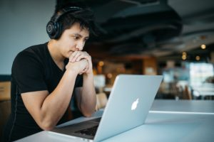 man wearing headphones while sitting on chair in front of MacBook