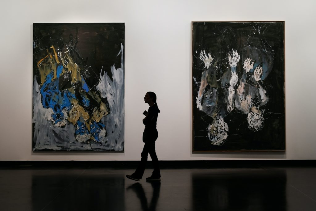 silhouette of person in front of abstract paintings